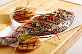 A whole, grilled bream with jalapenos, herbs and potatoes