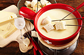 Swiss cheese fondue in a rechaud with a glass of kirschwasser and bread