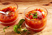 Spicy tomato chutney in jars with basil