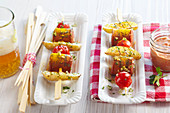 Grilled sausage and potato skewers with a tomato dip, curry and beer