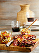Grilled beef steak with bacon, onions and corn salad with cheese (Mexico)