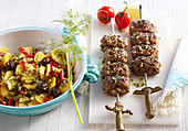 Grilled gyros kebabs with Greek potato salad with olives, tomatoes and lemon