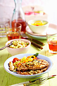 Grilled marinated pork collar steaks with cucumber salsa, potato salad and white beans