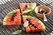 Sliced grilled watermelon with balsamic cream and pineapple sage