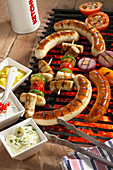 Sausages and sausage skewers on a grill with a trio of dips