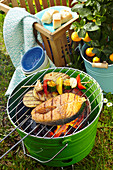 Marinated Cajun salmon, vegetables skewers and spicy potatoes on a barbecue
