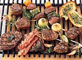 Various game meats and vegetables on a grill rack