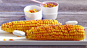 Marinated, grilled corn cobs with a pepper salsa