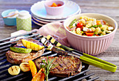 Marinated beef steaks with vegetables on a grill rack and a pasta salad