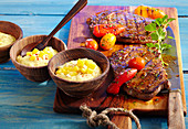 Two marinated, grilled club steaks with a mango dip, peppers and tomatoes