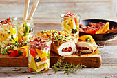 Grilled chicken breast with a Mediterranean filling and pasta salad in glasses