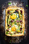 Puff pastry tart with vegetables, egg and pine nuts