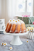 A lemon Bundt cake decorated with daisies for a birthday