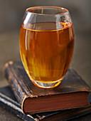 Ein Glas Whisky auf gestapelten alten Büchern