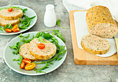 Baked turkey meatloaf with mortadella and aromatic herbs served with rocket and tomatoes