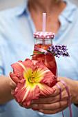 Hände halten Taglilien Blüte und Trinkflasche mit Lavendelsträußchen