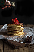 Person pouring maple syrup on appetizing tasty stack of pancakes with ripe strawberry