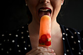 Woman in black dress licking delicious refreshing fruit popsicle with ripe berries