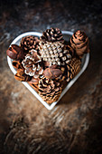 Various pine cones etc. in heart-shaped bowl