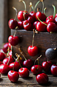 Cherries in a wooden crate and on a table