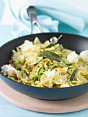 Farfalle in a pan with courgette, pine nuts, sage and mozzarella