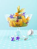 Orange salad with kiwi and purple edible flowers