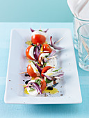 Tomato and mozzarella skewers with red onions and basil