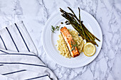 Baked salmon served on couscous with asparagus and caper on the side