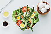 Served bowl of salad with asparagus eggs avocados tomatoes walnuts and greenery on table with condiments sauces and eggs