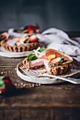 Erdbeer-Zitrusfrucht-Törtchen mit Essblüten, angeschnitten