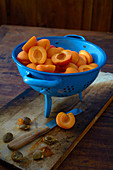 Fresh apricots, whole and pitted in a blue colander