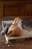 Baguette on a wooden board with a bread knife on a rustic wooden table