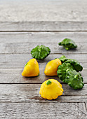 Mini yellow and green patty pan squash on a rustic wooden table