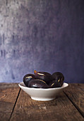 Ceramic bowl of ripe healthy figs placed on aged wooden table against blue wall