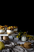 Assorted delicious desserts and snacks placed on table near napkin and flowers against black background