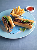A steak sandwich with caramelised onions, rocket and chips
