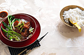 Slow cookes Chinese pork with sticky rice and stir-fried greens