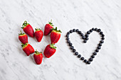 Strawberries and blueberries in heart shape, studio shot