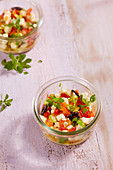 Mozzarella salad with tomatoes, spring onion, peppers, olive and basil in a glass