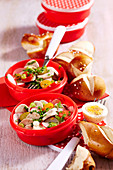 White sausage salad with lye bread rolls in plastic containers to take away