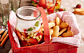 strawberry and apple punch with cider and sparkling wine in a picnic basket with biscuits