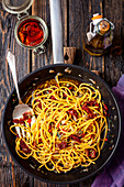 Spaghetti with dried tomatoes, capers, red onion and chili