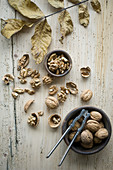 Organic walnuts, whole and cracked, in a bowl with a nut cracker on a rustic wooden surface