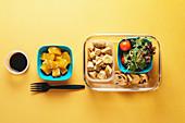 Gesunde Lunchbox mit Hähnchen, Salat und Orange