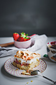 A slice of strawberry and rhubarb cake with meringue