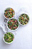 Colourful summer salads with prawns, fruit, mozzarella, olives and bulgur