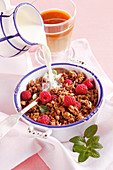 Chocolate muesli with raspberries, mint, yoghurt and milk