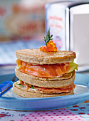 A stack of blinis with salmon and salmon caviar