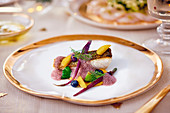 Fried zander fillet with blueberry foam, fruit and root vegetables