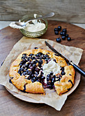 Blueberry tart with almonds and whipped cream